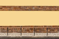 The yellow wall of the house, the sidewalk on the street, columns. royalty free stock photos