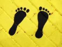 Yellow wall and two painted foot, Lithuania royalty free stock photo