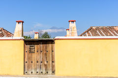 Yellow wall & two volcanoes, Antigua, Guatemala. Yellow wall & gateway with volcanoes Fuego & Acatenango in distance in colonial city & UNESCO World Heritage stock photo