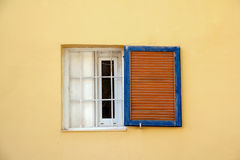 Yellow Wall, White Window, Blue Shutters. Yellow stucco or plaster wall with white wooden framed window and blue and red shutter Stock Images