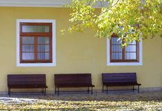 Yellow wall with windows and benchs Stock Photo