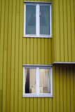Yellow wall wooden  house two white windows Royalty Free Stock Photo