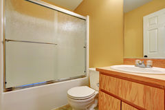 Yellow walls bathroom with glass screened shower bathtub. Toilet and wooden vanity cabinet. Northwest, USA Royalty Free Stock Image