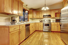 Yellow warm wood kitchen with new floor. Stock Photography