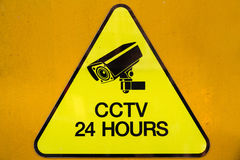 Yellow warning cctv security cameras sign operating 24 hour Stock Photography