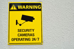 Yellow warning cctv security cameras sign. A yellow warning cctv security cameras sign stating that there is cctv cameras in the area operating 24/7. concept Royalty Free Stock Photo