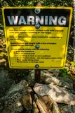 A yellow warning placard for hikers in Acadia NP, Maine. Acadia National Park, ME, USA - August 15, 2018: A nearly vertical route trail caution signboard stock images