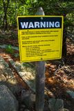 A yellow warning placard for hikers in Acadia NP, Maine. Acadia National Park, ME, USA - August 15, 2018: A nearly vertical route trail caution signboard royalty free stock images