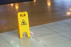 Yellow warning plate wit Caution wet floor icon on slippery tile floor st shopping mall indoors.  Stock Photos