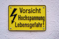 Yellow warning sign that alarms us for high voltage Switzerland. Yellow warning sign against a white wall that alarms us for the possible danger of a high stock images