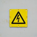 Yellow warning sign on a gray wall Stock Photo