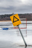 Yellow warning sign and hockey goal on wet melting ice on frozen lake, Sweden. Royalty Free Stock Photo