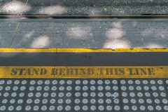 Warning sign. Yellow warning sign near tram line Royalty Free Stock Photography