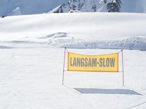 Yellow warning sign on the ski piste. Warning sign on the ski piste showing the word slow Stock Photography