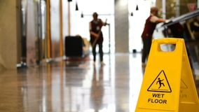 Yellow warning sign wet floor. stock video footage