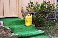 Yellow water bucket jug placed on stone steps in front of cottage door Royalty Free Stock Photography