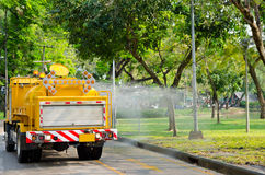 Yellow water cart. Yellow truck - water cart - pours water on road and lawn Stock Image