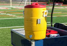 Yellow water cooler on a blue cart with soccer net in background. A yellow water cooler sits on a blue golf cart during a soccer game at a local high school on a Stock Images