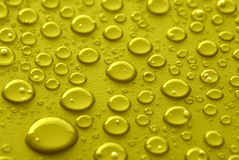 Yellow water drops Stock Images
