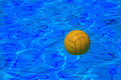 Yellow water polo ball on water background. Yellow water polo ball on blue water background royalty free stock photo