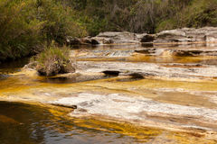 Yellow water river on quartzite. Rocks royalty free stock photo