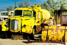 Yellow Water Truck. Rusting and becoming decrepit in a desert junk yard Royalty Free Stock Photos