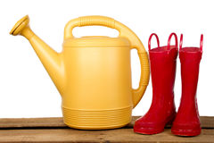 Yellow Watercan and Red Boots Royalty Free Stock Images