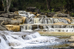 Yellow waterfall in sunny day Stock Photos