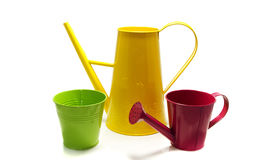 Yellow watering can en green pot Stock Images