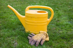 Yellow watering can and glows Royalty Free Stock Photos