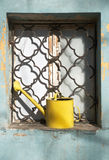 Yellow watering can in  grated window of old house Royalty Free Stock Images