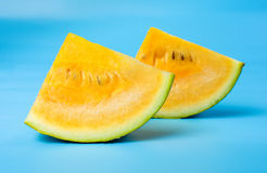 Yellow watermelon slice against blue background Royalty Free Stock Photography