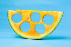 Yellow watermelon slice against blue background Stock Image