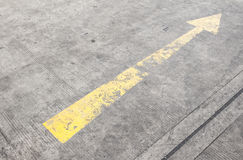 Yellow way arrow pointing  symbol on a ground road surface Stock Image