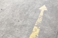 Yellow way arrow pointing  symbol on a ground road surface Royalty Free Stock Image