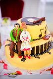 Yellow wedding cake figures of a bride and groom Stock Photography