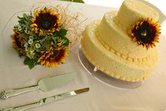 Yellow wedding cake with flowers. Big yellow wedding cake with sunflower bouquet on table with cake knives Stock Image