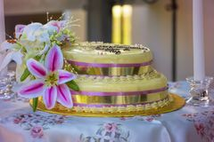 Yellow And Purple Trimmed Wedding Cake. Yellow wedding cake trimmed with purple and gold ribbon and decorated with orchids Royalty Free Stock Images