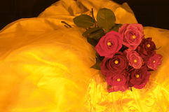 Yellow Wedding dress. Wedding dress and roses in yellow lighting Royalty Free Stock Photography