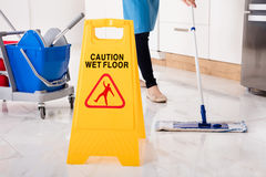 Yellow Wet Caution Sign On Wet Floor In Kitchen. Close-up Of Yellow Wet Caution Sign On Wet Floor In Kitchen Stock Image