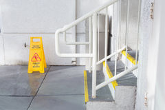 Yellow Wet Floor Sign Warning Of Slippery. Near staircase Royalty Free Stock Images