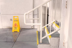 Yellow Wet Floor Sign Warning Of Slippery. Near staircase Stock Photos
