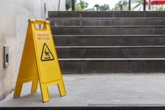 Yellow wet floor warning sign on the floor in hotel Stock Images