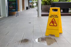 Yellow wet floor warning sign on the floor in hotel Stock Photo