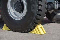 Yellow wheel chocks under the big truck wheels. Yellow wheel chocks under the big black truck wheels in summer royalty free stock images