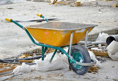 Yellow wheelbarrow on a construction site Stock Images