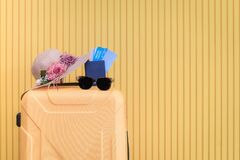 Free Yellow Wheeled Luggage Is Placed In A Room With A Knitted Hat Decorated With Flowers, Passports, Plane Tickets And Sunglasses To T Stock Image - 185375751