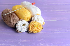 Yellow and white beaded crochet roses, skeins of cotton yarn, crochet hook on wooden background. Easy colored flowers patterns Royalty Free Stock Photo