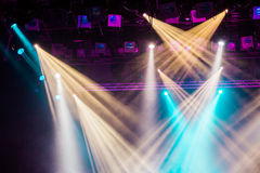 Yellow, white, and blue light rays from the spotlight through the smoke at the theater or concert hall Royalty Free Stock Image