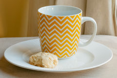Yellow and White Chevron Patterned Mug on Plate with Cookie Royalty Free Stock Images